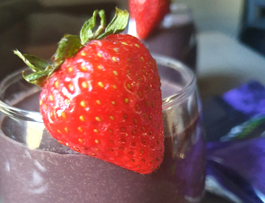 healthy acai fruit smoothie with a bright red strawberry garnish